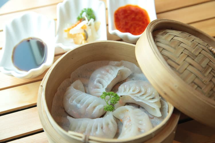 Home made cultural asian dishes including Chinese dumplings in a traditional bamboo steamer