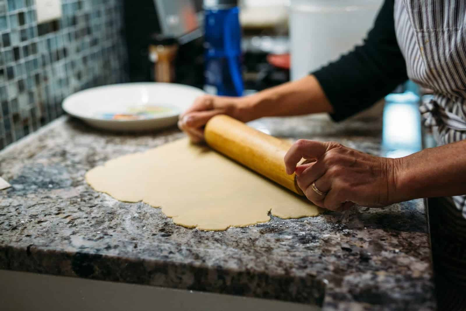 Immigrant woman rolling dough in her kitchen showcasing the impact of home cooking gig economy for immigrants