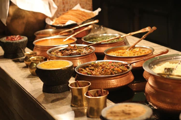 Homemade traditional Indian dishes served in copper pots and stone bowls
