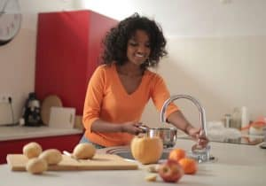 Smiling-young-ethnic-lady-cooking-in-her-home-kitchen