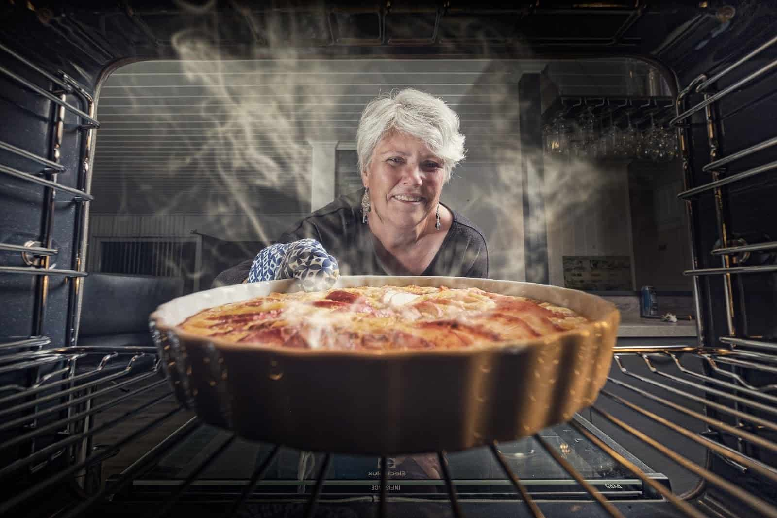 Freshly baked pie taken out of the oven by older women for her home-based cooking business