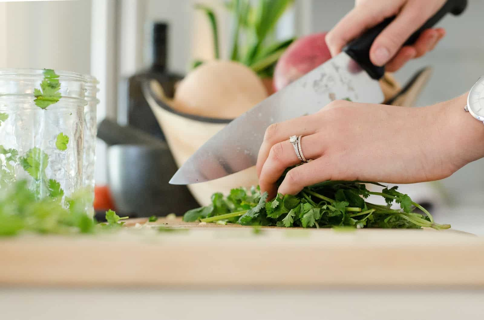 Woman chopping up fresh vegetables on a cutting board