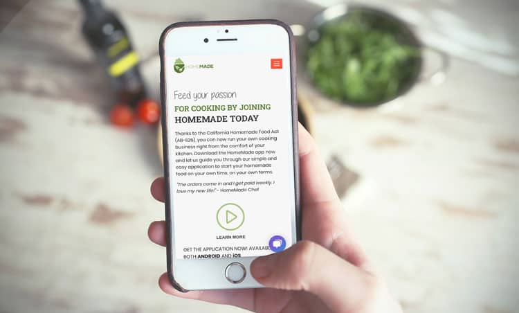 White iphone showing homemade food app in front of fresh vegetables in home-based restaurant
