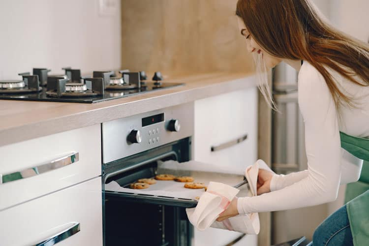 Woman Taking Baked Cookies Out of the Oven